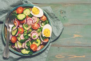 Vegetarian salad of fresh vegetables on a rustic green background. Top view, space for text.