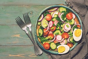 Vegetable salad with boiled egg served on a plate. Green rustic background, forks, napkin. Top view, copy space. Toned photo