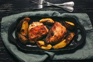 Baked chicken thighs with potatoes on a rustic dish. Dark background, top view, flat lay