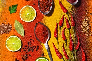 A variety of bright spices. Spices in spoons. Beautiful bright background of spices. View from above.