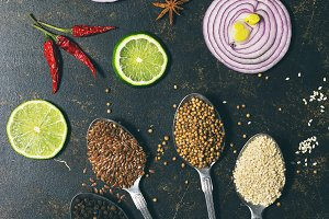 Various spices in spoons, coriander, sesame seeds, flax seed, peppercorns on a dark background. Slices of red onion and lime. View from above. flat lay
