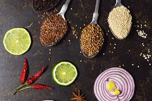 Spices in spoons on a dark background. Red onion slices, lime, bell pepper, sesame, flaxseed, coriander. Top view, vertical frame. Flat lay