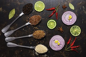 Spices in spoons on a dark background. Red onion slices, lime, bell pepper, sesame, flaxseed, coriander. View from above. flat lay