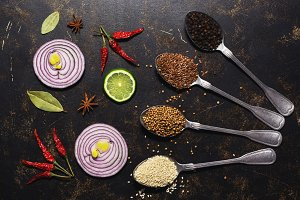 Spices in spoons, coriander, sesame seeds, flax seed, peppercorns on a dark background. Slices of red onion and lime. View from above. flat lay