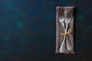 Two vintage forks tied with linen thread on a blue background. Space for text, lay flat