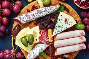 Assorted variety of snacks with red wine. Various sausages and cold meat, cheese with mold, fruit. Top view, flat lay