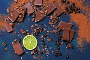 Lime slice with pieces of chocolate and fried coffee beans on a blue background. View from above