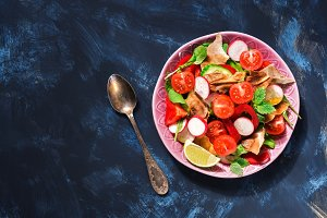Arabic salad of fresh vegetables with bread Fattoush on a blue background. Top view, copy space