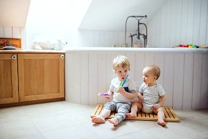 Two toddler children brushing teeth in the bathroom at home.