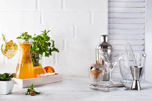 Orange lemonade in the decanter on a wooden tray and Cocktail shaker for preparing a summer cocktail with a place for your subject and text