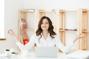 Business and Health Concept: Portrait young woman near the laptop, practicing meditation at the office desk, in front of laptop, online yoga classes, taking a break time for a minute.