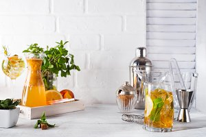 Orange lemonade in the decanter on a wooden tray, cocktail glass with ice, mint and ginger and Cocktail shaker with a place for your subject and text