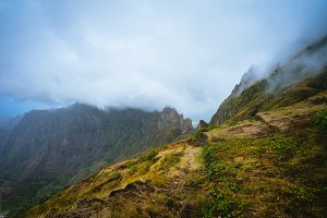 Trekking path beside the mountain peak chain overgrown with verdant grass and cultivated plants. Foggy clouds moving over the Mountain edge. Xo-Xo Valley. Santo Antao Island, Cape Verde Cabo Verde