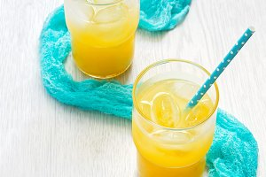 Fresh orange juice, blue napkin, straws on a white wooden table. Selective focus. The concept of summer and holidays