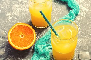 Orange juice in a glass with a blue napkin on a gray background. Selective choice. The concept of summer. Toned photo