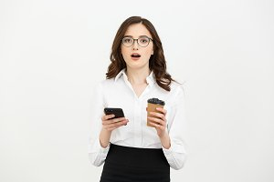 Portrait of a shocked surprised businesswoman in eyeglasses holding take away coffee cup and mobile phone while standing isolated over gray background.