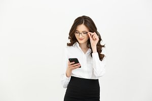 Business Concept: Portrait of Business woman wearing white shirt using a mobile phone isolated on a white background.