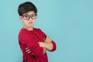 angry boy with glasses on blue backg