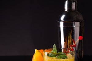 Fresh cocktail with orange, mint and ice on black glass backgorund
