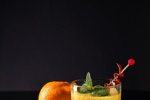 Fresh cocktail with orange, mint and ice on black glass backgorund, copy space