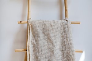 Tablecloth textile on wooden hanger in the background a white wall