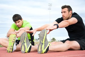 two men stretching in running track