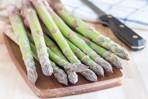 Green asparagus on wooden board