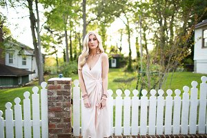 Blonde girl standing by fence