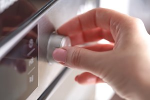 female hand using the microwave