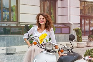 a girl is standing near a moped