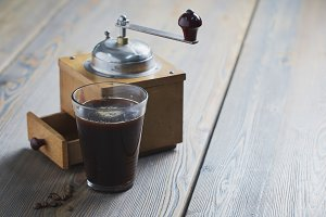 Black coffee with coffee grinder placed