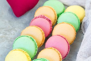 Different kinds of colorful french dessert macaron with different fillings on table, vertical
