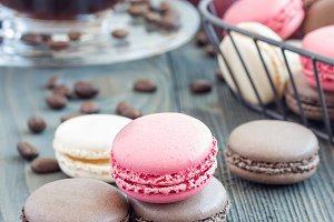 Different kinds of colorful french dessert macaron with different fillings on wooden table, served with coffee, square