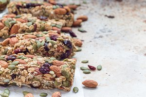 Homemade granola energy bars with figs, oatmeal, almond, dry cranberry and pumpkin seeds, healthy snack, copy space, horizontal