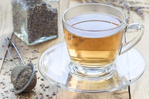 Healthy herbal lavender tea in glass cup with lavender flowers on background, horizontal