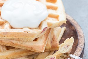Homemade savory belgian waffles with bacon and shredded cheese, served with plain yogurt on wooden plate, vertical, copy space
