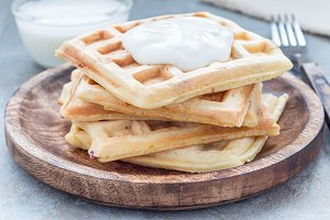 Homemade savory belgian waffles with bacon and shredded cheese, served with plain yogurt, on wooden plate, horizontal