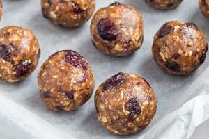 Healthy homemade energy balls with cranberries, nuts, dates and rolled oats on tray, horizontal