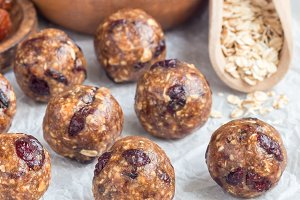 Healthy homemade energy balls with cranberries, nuts, dates and rolled oats on a parchment, square format
