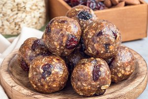 Healthy homemade energy balls with cranberries, nuts, dates and rolled oats on a wooden plate, square