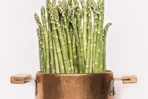 Asparagus in cooking pot on white