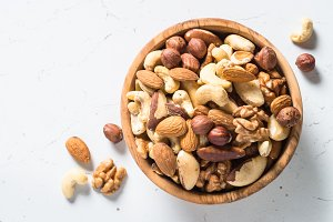 Nuts assortment in a bowl on white top view.