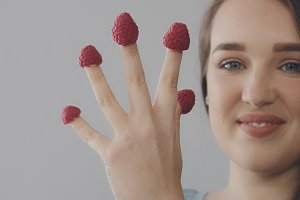 young caucasian woman with straight long hair eats raspberry from fingers