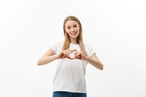 Isolated portrait of beautiful caucasian woman make heart symbol by hands. White studio background. Copy Space.