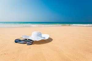 hat, sun glasses and flip flops over the sand