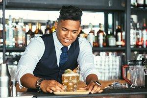 Smiling bartender presents a cocktai
