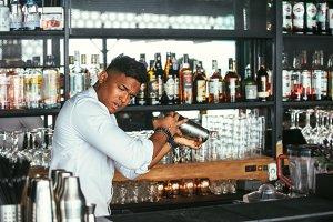 Expert barman shakes a cocktail