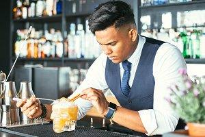 Expert barman decorating a cocktail