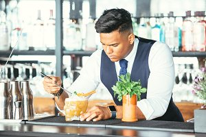 Expert barman decorates a cocktail