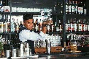 Expert barman adds alcohol